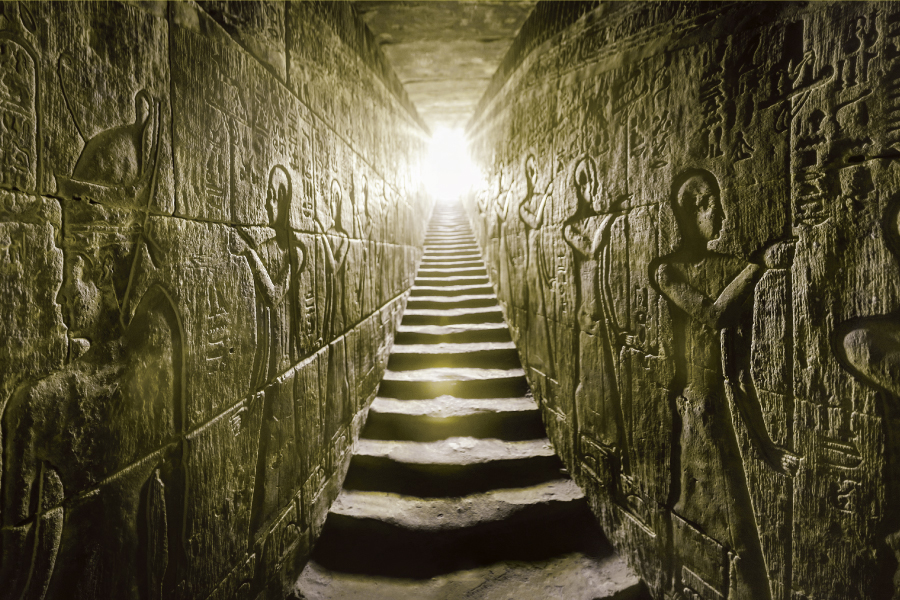 Passage flanked by two glowing walls full of Egyptian hieroglyphs